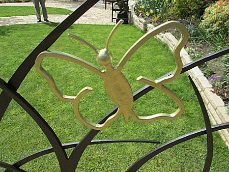 ornamental metal garden fence with grass and butterflies